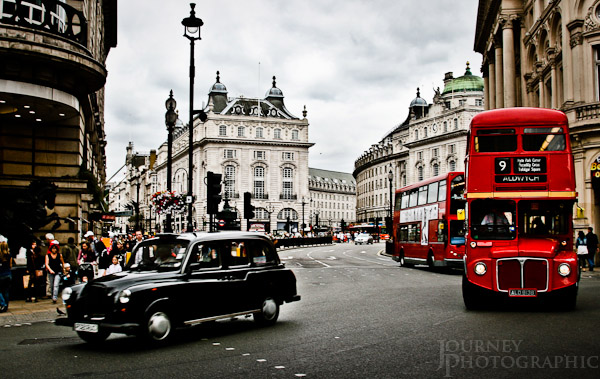 Picture of black cab and red buses in Piccadilly Circus, London