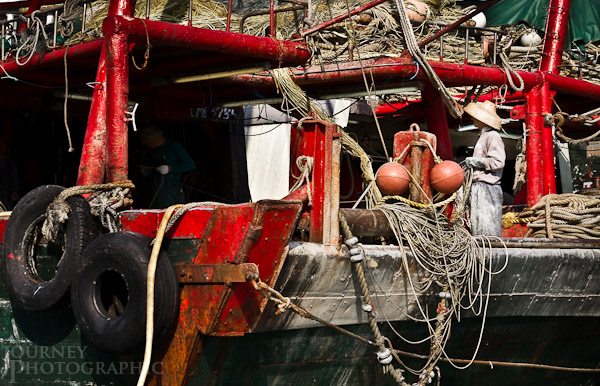 Picture of a man on a fishing boat in the floating village of Aberdeen, Hong Kong