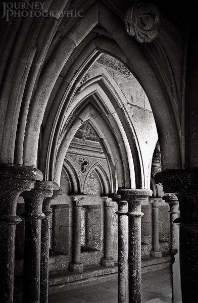 Black and white picture of the arches in the cloisters of Mont St Michel Abbey, Normandy, France
