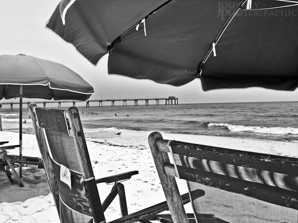 Black and white picture of a beach, with umbrellas, chairs, and a pier, Florida, USA