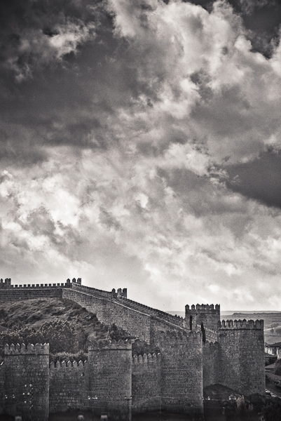 Black and white picture of clouds over the medieval walls of Avila, Spain