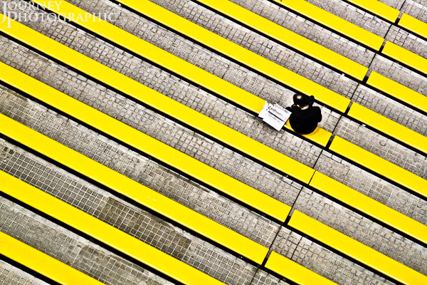 Picture of man sitting in rows of yellow seats, Sha Tin Racecource, Hong Kong