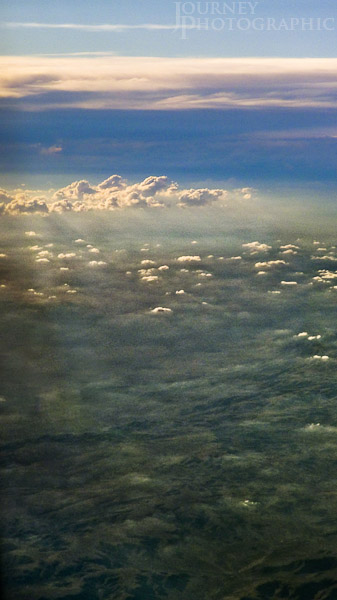 Landscape picture looking down through clouds from 30,000ft
