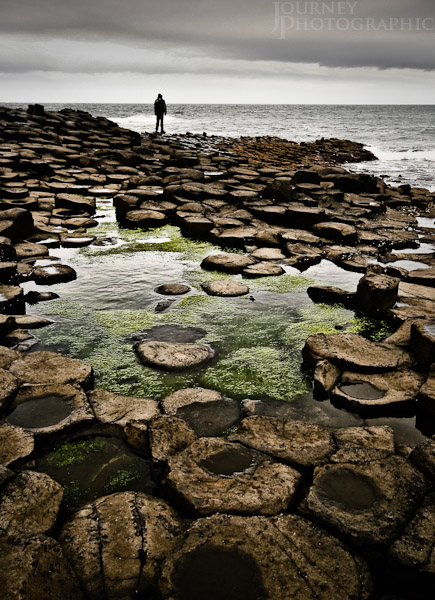 Picture of a person standing on the edge of the Giant's Causeway, Northern Ireland