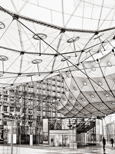 Black and white picture of man under the sails of the Grand Arch, La Defence, Paris