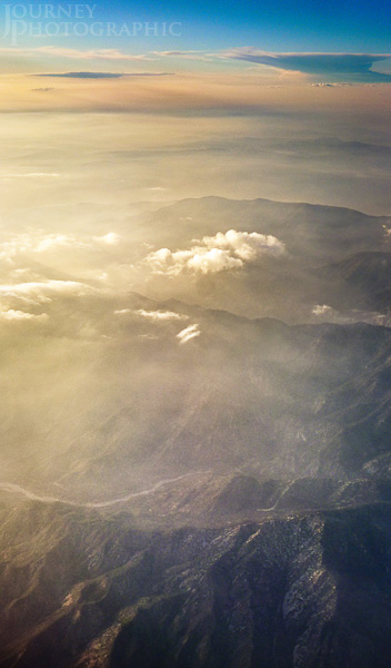 Picture of an aerial landscape looking down at mountains through clouds, USA