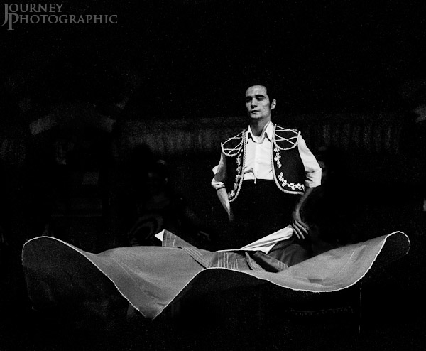 Black and white picture of male flamenco dancer swirling his cape, Seville, Spain