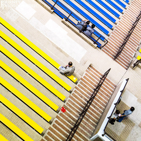 Colourful, geometric picture of people sitting on seats at Shar Tin racecourse, Hong Kong,