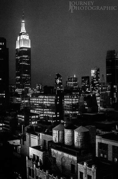 Black and white picture of the Empire State Building and water towers at night, New York