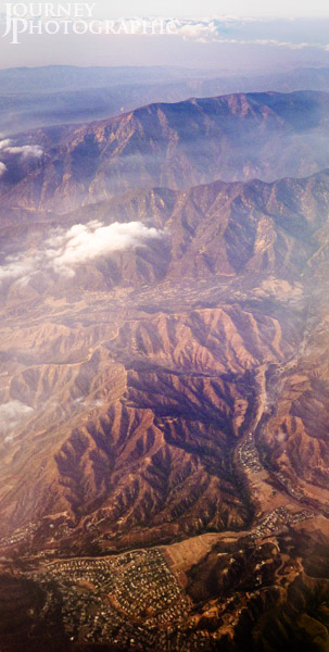 Aerial picture of mountains, clouds and town from 30,000ft, California, USA