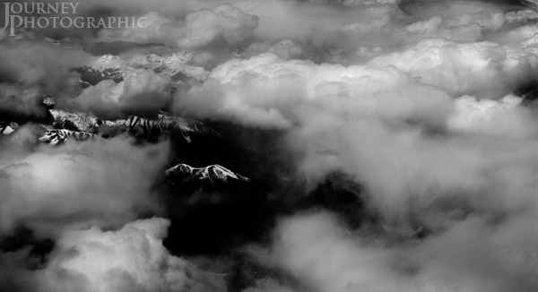 Black and white aerial landscape picture of Rocky Mountains through clouds, Colorado, USA