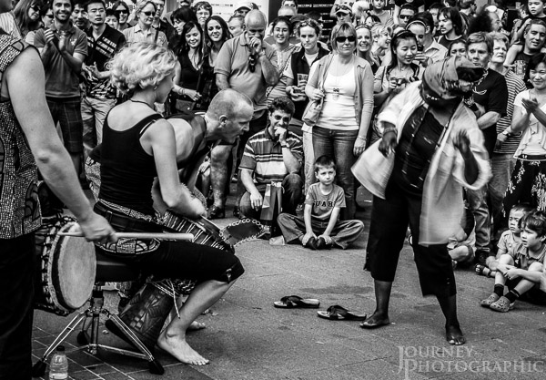 Black and white picture of buskers drumming and lady dancing, Canberra, Australia