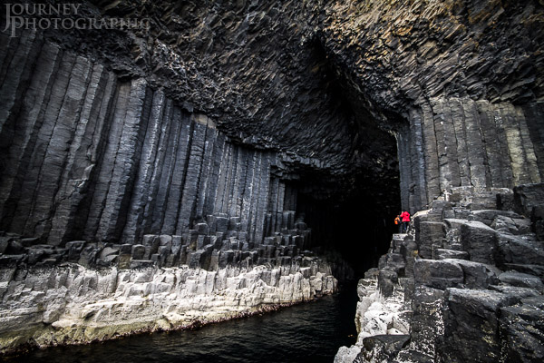 Landscape picture people in front of the entrance to Fingal's Cave, Staffa Island, Scotland