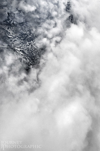 Black and white landscape picture of aerial view through clouds, USA