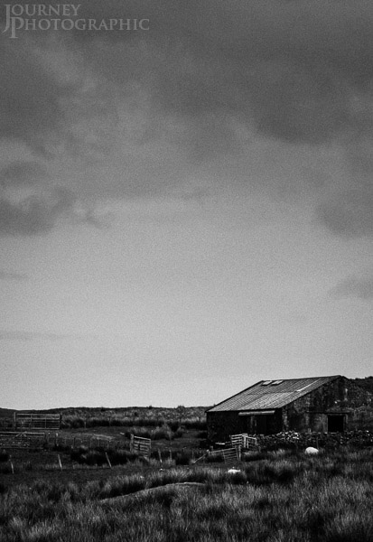 Black and white landscape picture of scottish hut and clouds, Scotland
